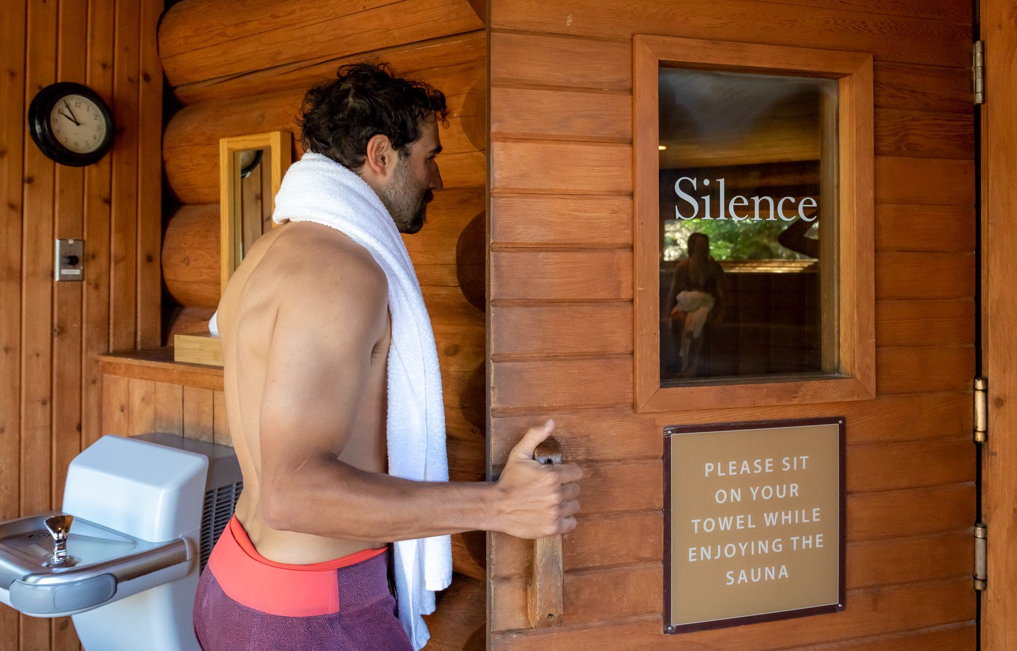 Man opening sauna door with silence printed on the glass