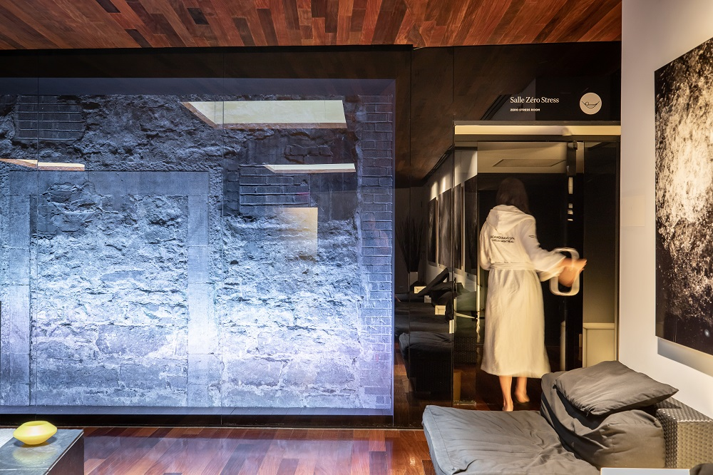 A woman in a robe leaving the Zero Stress Room of the Scandinave Spa Old Montreal.