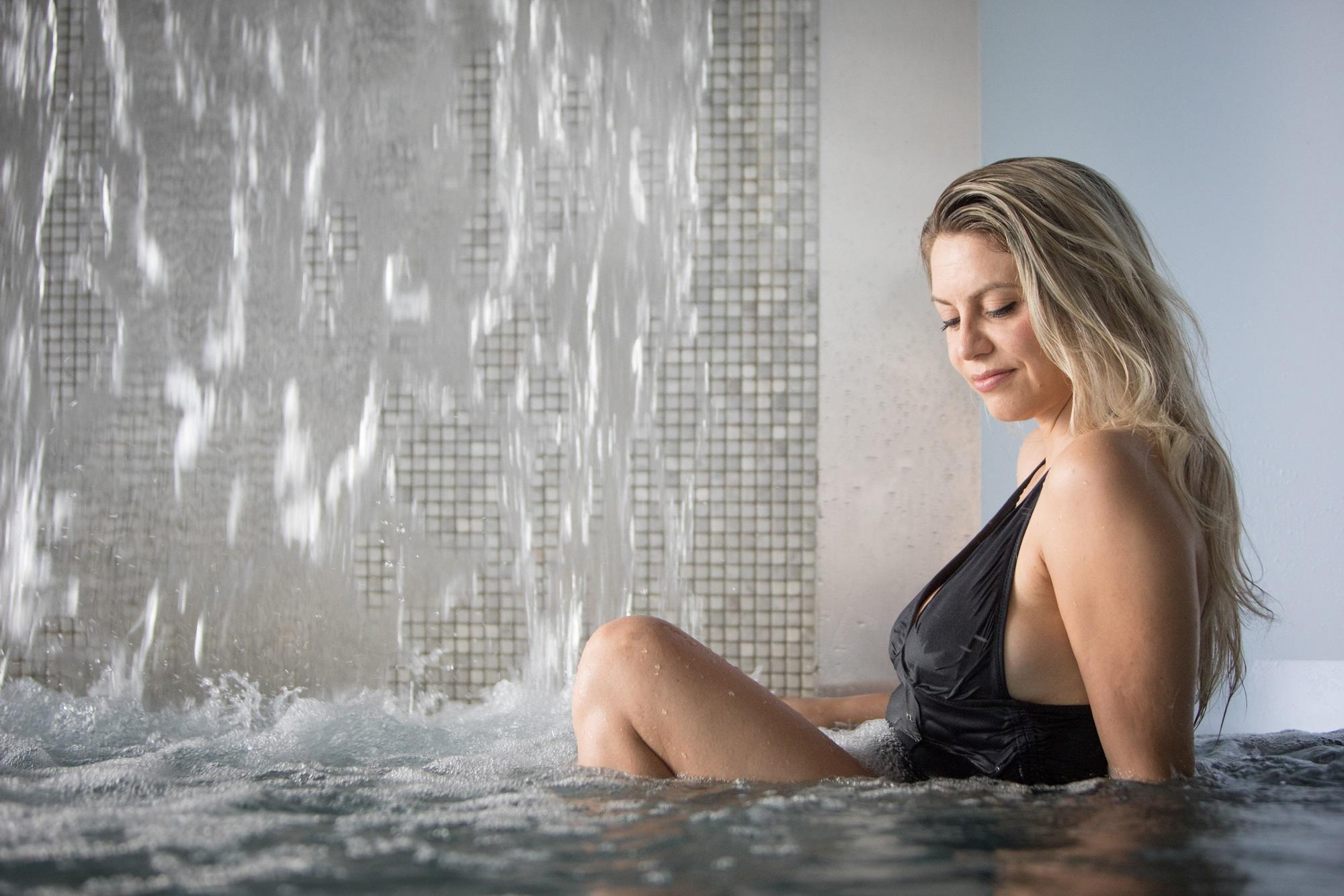 A woman sitting near the thermal waterfall of the Scandinave Spa Old Montreal.