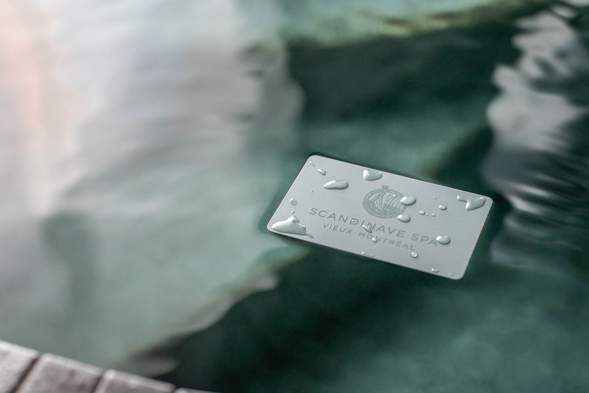 A Scandinave Spa Old Montreal membership card floating on the water.