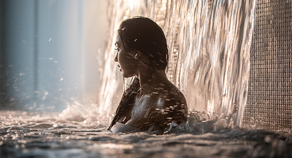 A woman standing under the thermal waterfall of the Scandinave Spa Old Montreal.