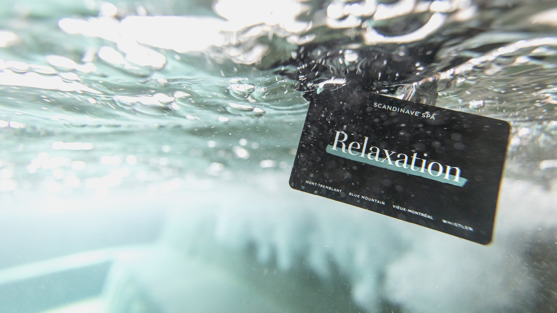 A Scandinave Spa Old Montreal membership card in the water.