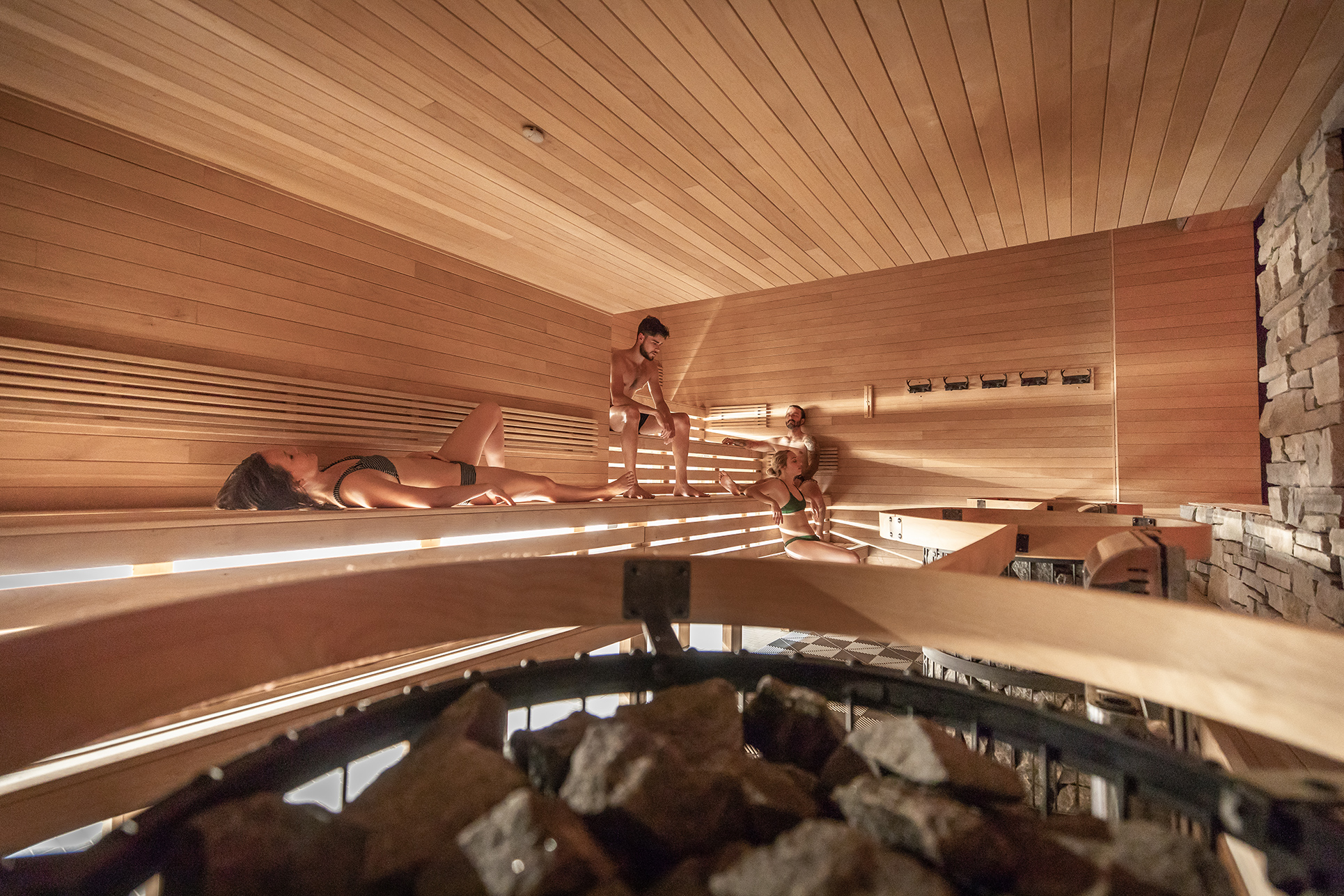 Four guests enjoying a warm Finnish dry Sauna at Scandinave Spa Tremblant.