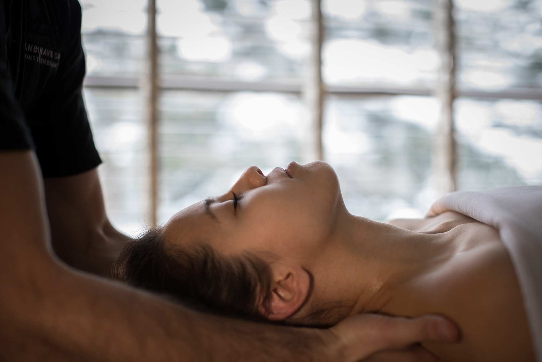 A woman getting a shoulder massage by one of the registered massage therapists at Scandinave Spa Tremblant..