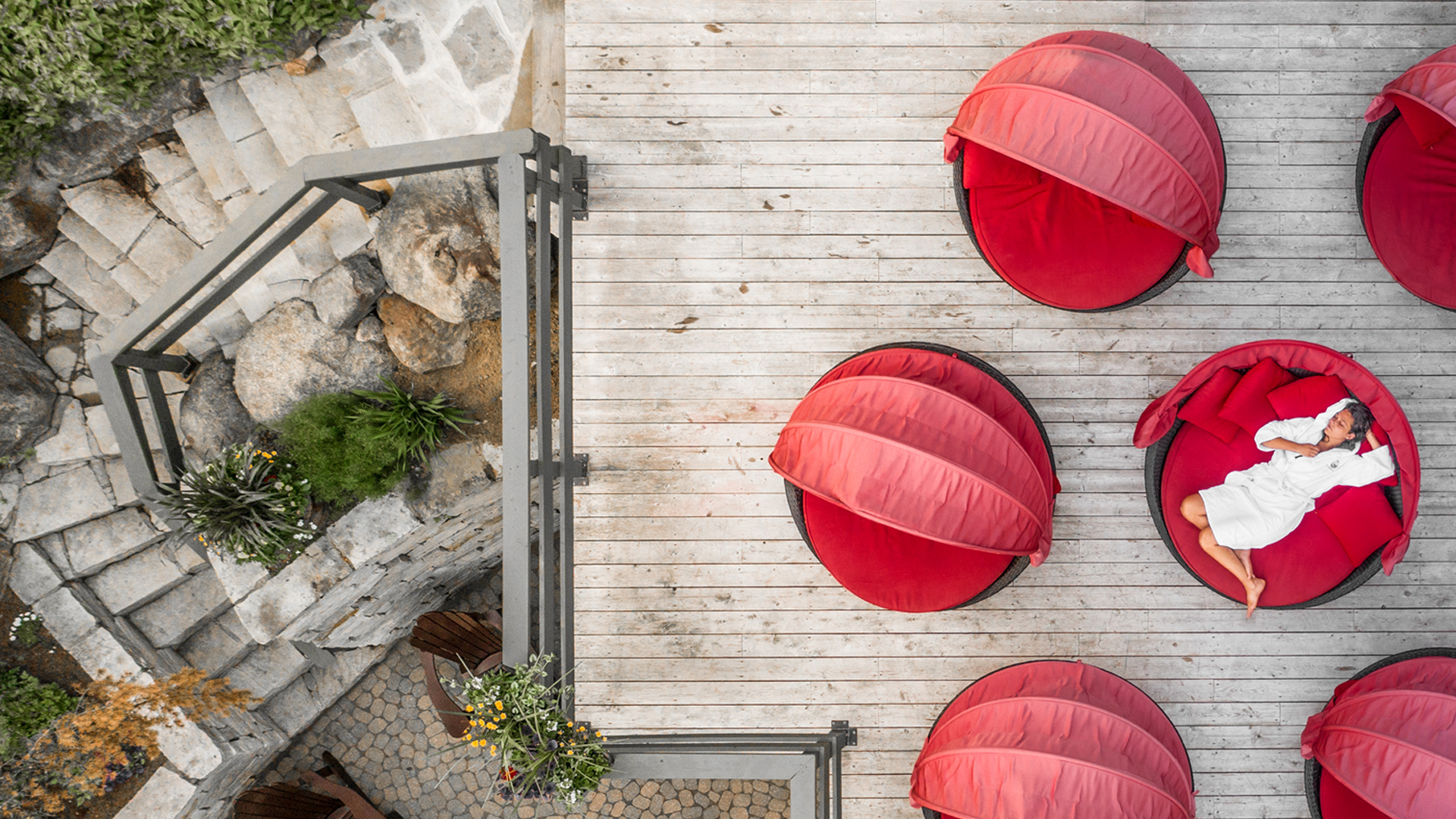 A bird's eye view of the Scandinave Spa Tremblant relaxing area with a woman laying down on the red sofas.