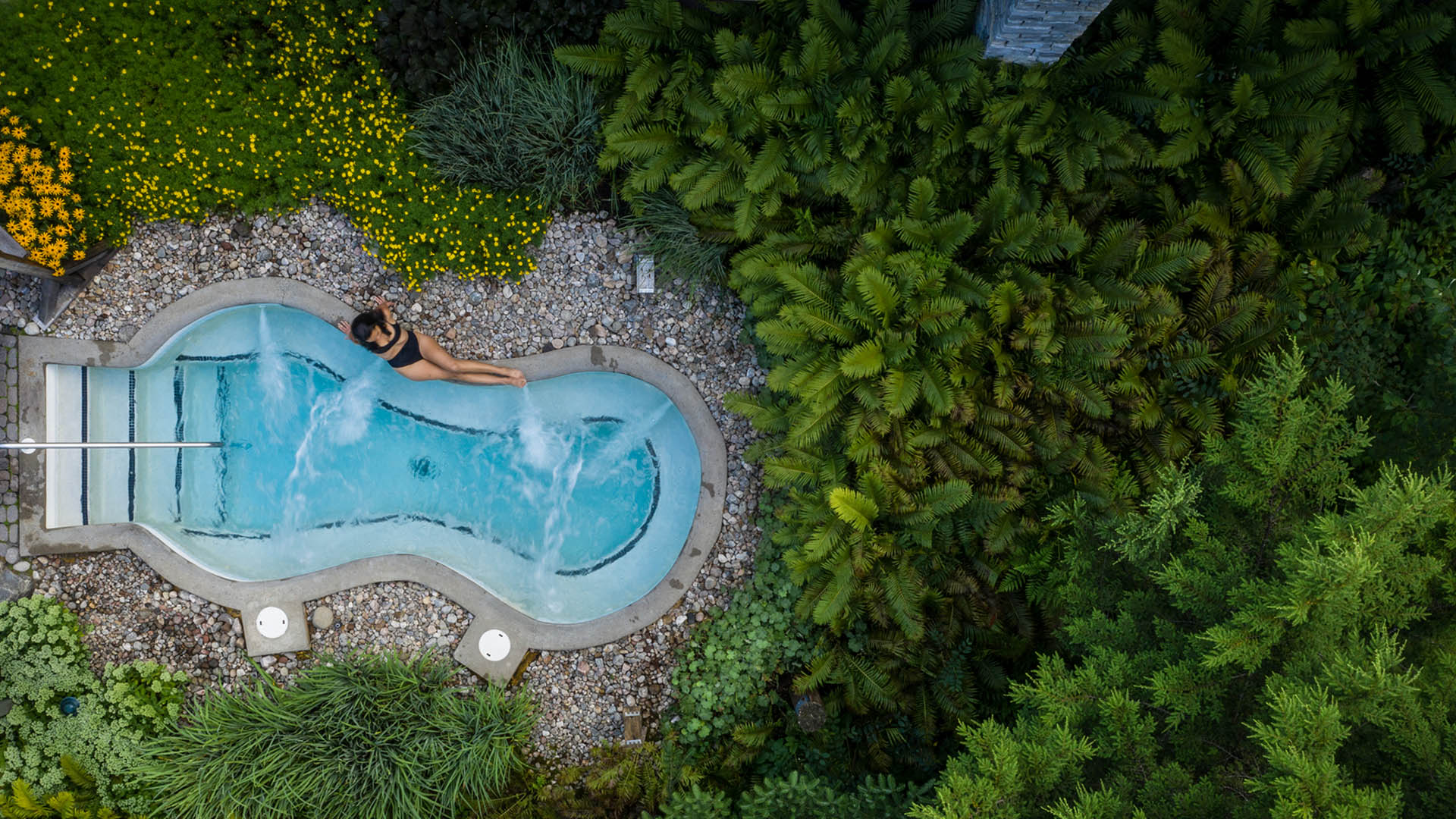 A bird's eye view of a woman laying down and relaxing by one of the Scandinave Spa Tremblant baths.