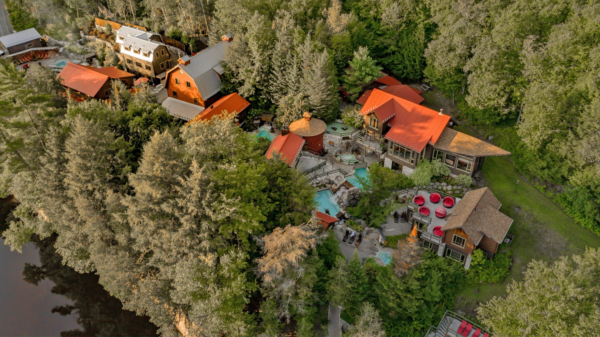 A bird's eye view of the Scandinave Spa Tremblant and the surrounding forest on a clear summer day.