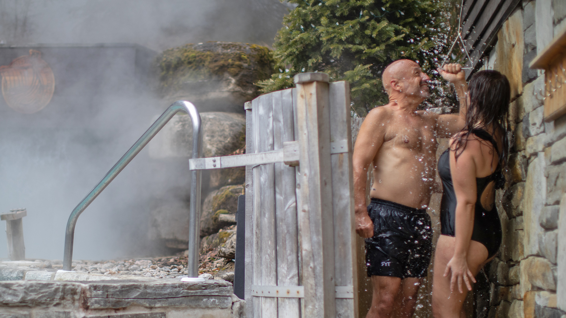 A couple standing under the shower of the Scandinave Spa Tremblant.