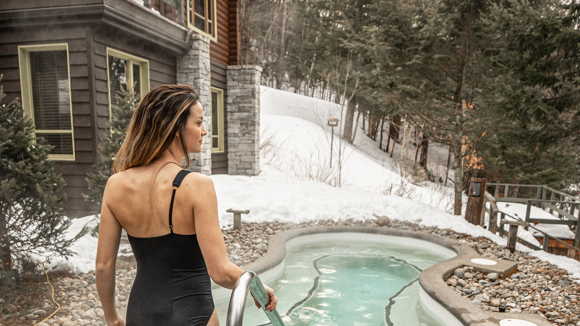 A woman walks into a hot bath at Scandinave Spa Mont-Tremblant.