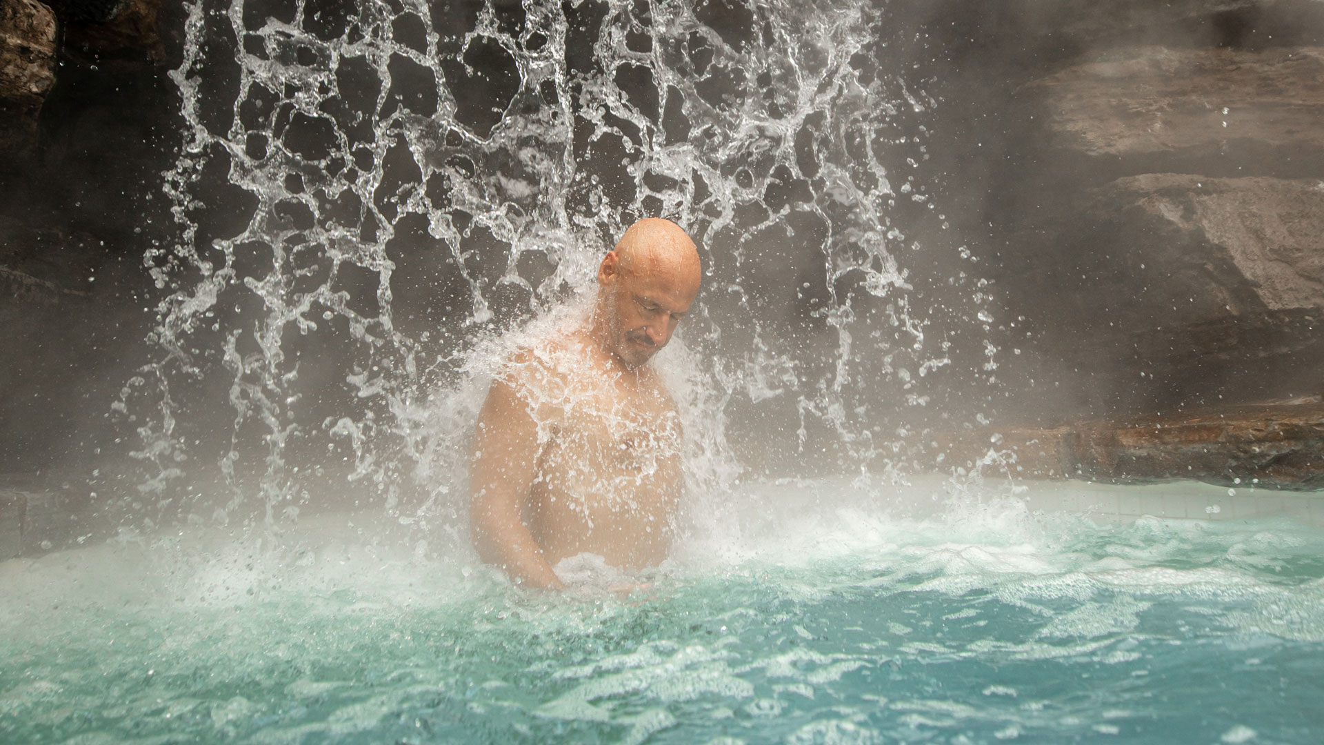 A man relaxes under the thermal waterfall at Scandinave Spa Mont-Tremblant.