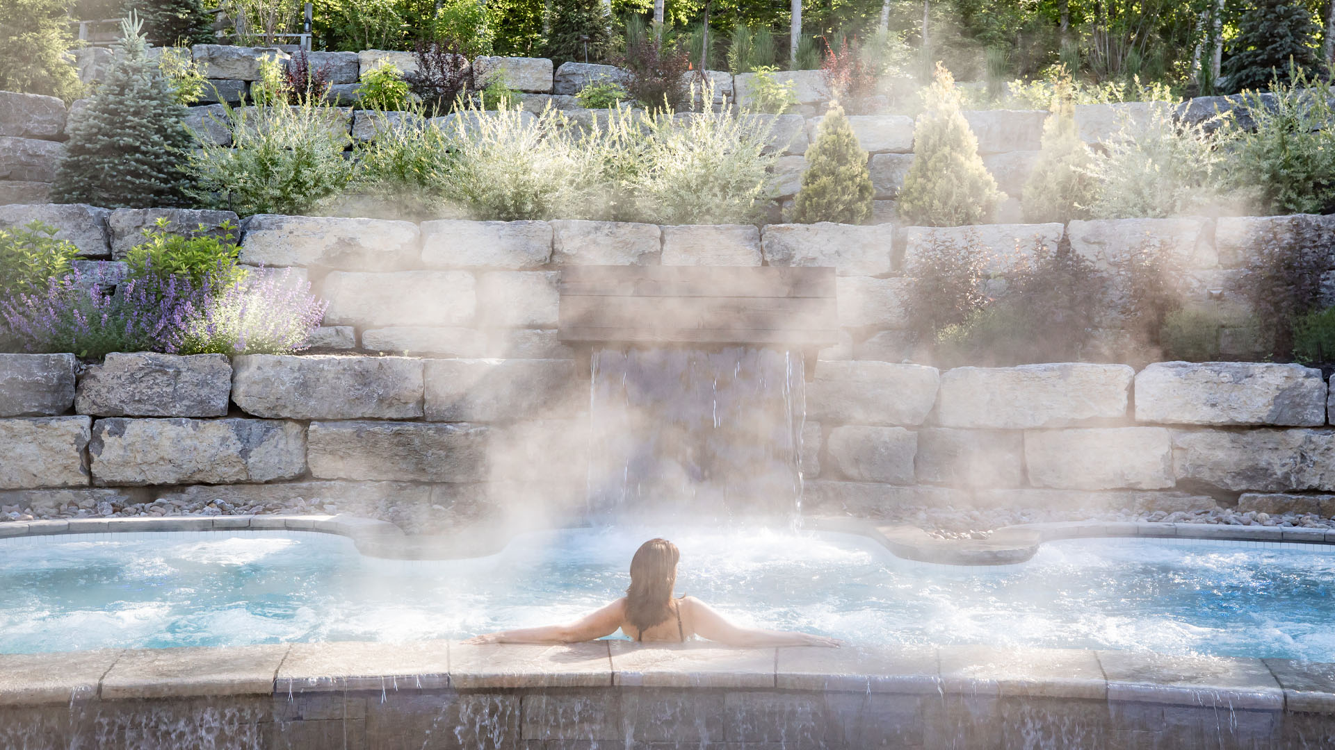 A woman enjoys the sunshine in the Infinity pool at Scandinave Spa Mont-Tremblant.