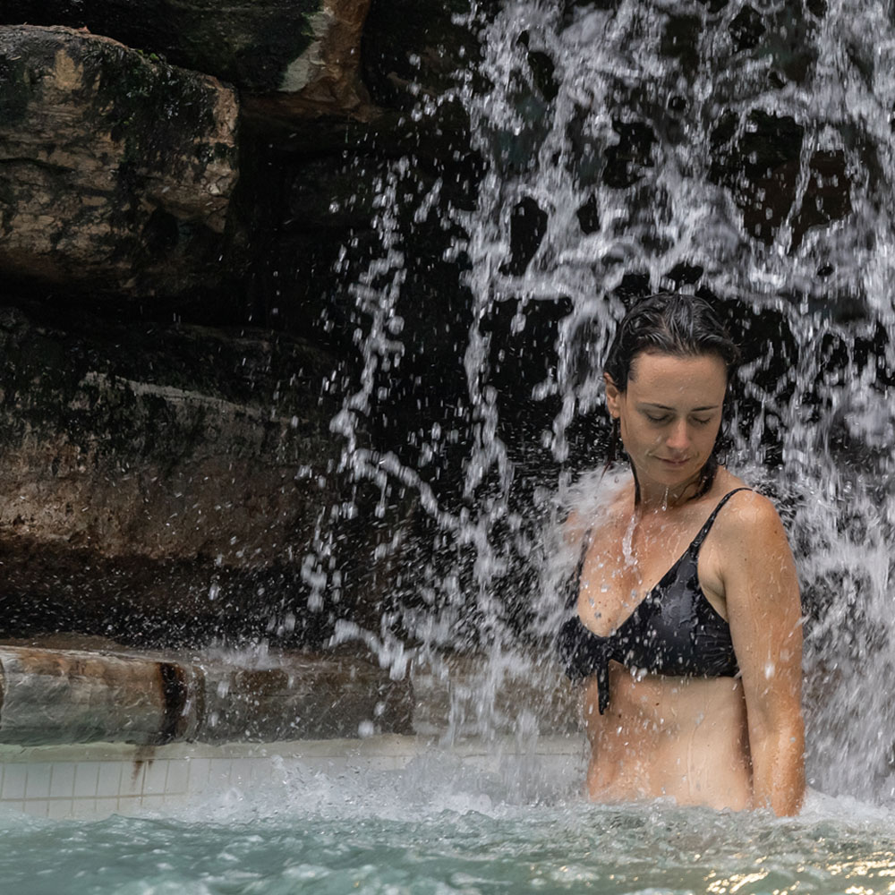 A woman enjoys the thermal waterfall at Scandinave Spa Tremblant.