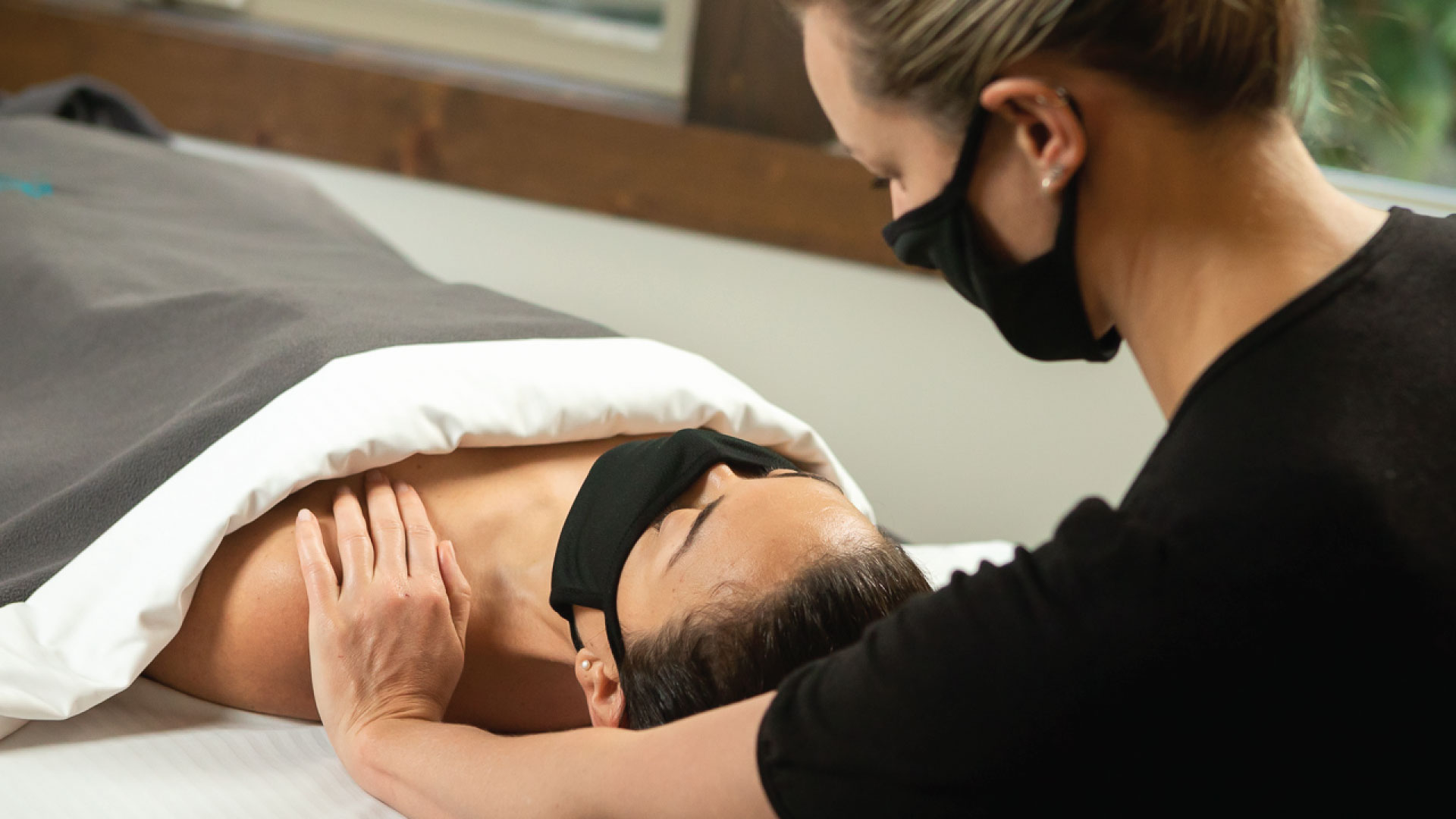 Woman giving a massage. Both people are wearing masks for COVID 19 safety at Scandinave Spa