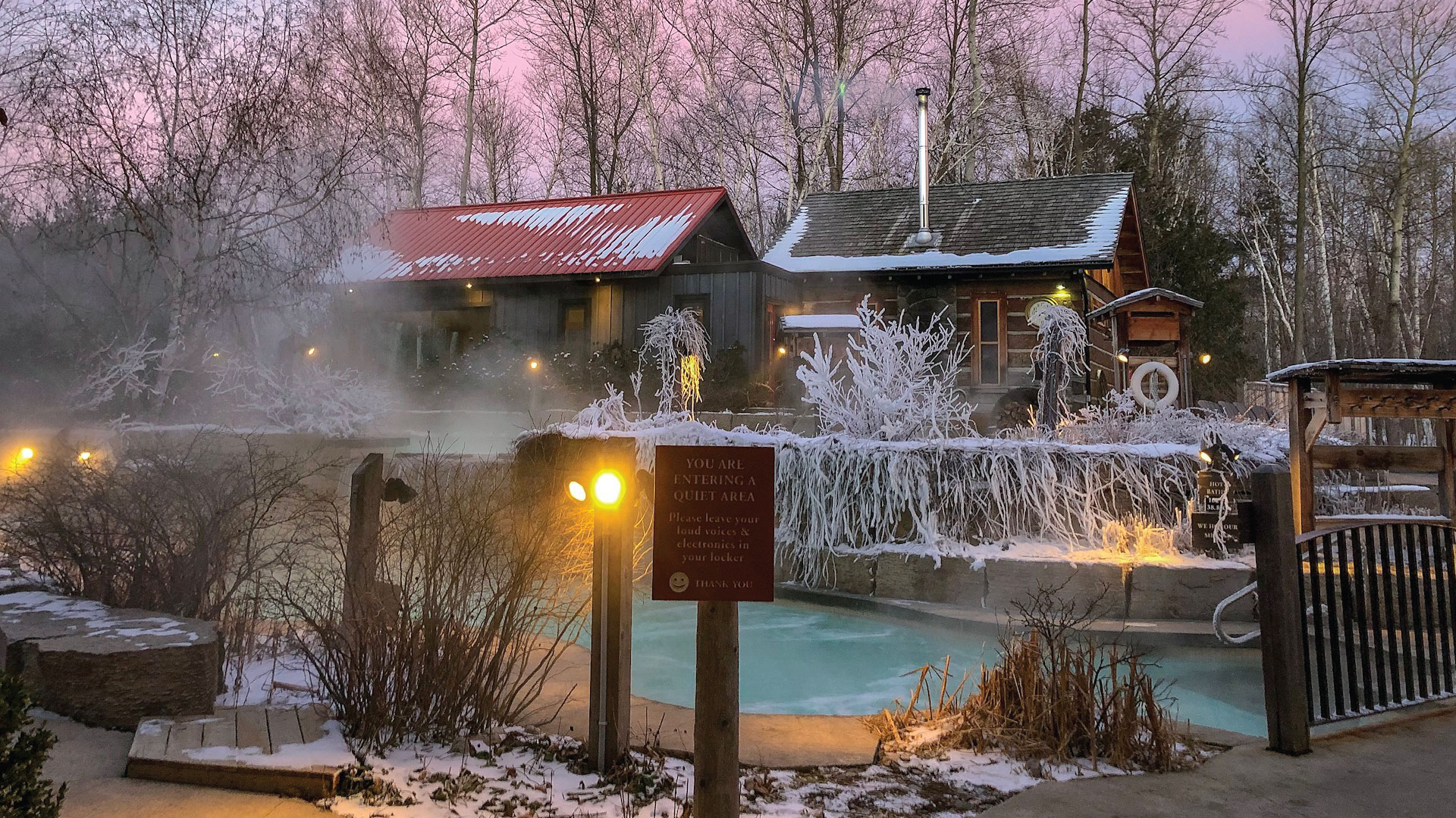Dusk falls on Scandinave Spa Blue Mountain, the trees are covered in snow and ice.
