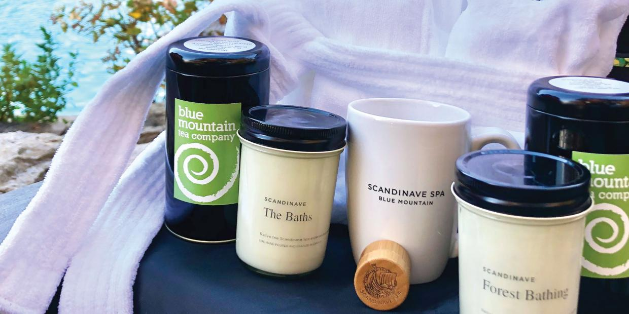 Scandinave Spa Blue Mountain specialty tea, candles, a ceramic tea mug next to a cozy Bath Robe in fall.